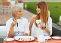 Mother and daughter adult drinking tea or coffee talking outdoors Stock Photography