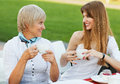 Mother and daughter adult drinking tea or coffee talking outdoors Stock Image