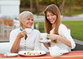Mother and daughter adult drinking tea or coffee talking outdoors Stock Photos