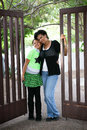 Mother and daughter african american standing in a park near a gate Royalty Free Stock Images