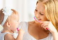 Mother and daughter baby girl brushing their teeth together happy family health Stock Photos