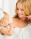 Mother and daughter baby girl brushing their teeth together happy family health Royalty Free Stock Photo