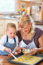 Mother and daughter baking cookies together with the family coat self made with a brush Stock Photography