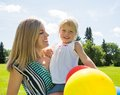 Mother and daughter with balloons in park happy mid adult helium Royalty Free Stock Images