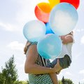 Mother and daughter with balloons in park side view of helium Royalty Free Stock Photography
