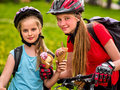 Mother and daughter bicycle. Family eating ice cream , ride bike . Royalty Free Stock Photo
