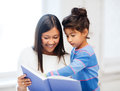 Mother and daughter with book family children education school happy people concept Stock Photo