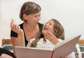 Mother and daughter with book portrait caucasian reading a at home smile Stock Image