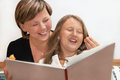 Mother and daughter with book portrait caucasian reading a at home smile Stock Images