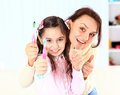 Mother and daughter brush their teeth Stock Photos