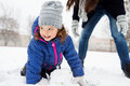 Mother and daughter building a snowman in winter nature Royalty Free Stock Photo