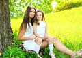 Mother and daughter child together sitting on grass near tree in summer Royalty Free Stock Photo