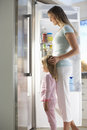 Mother and daughter choosing snack from fridge Stock Images