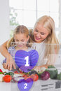 Mother and daughter chopping vegetables with purple holographic interface in the kitchen Royalty Free Stock Photo