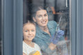 Mother and daughter cleaning window and smiling at camera