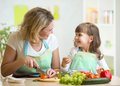 Mother and daughter cooking and cutting vegetables Royalty Free Stock Photo