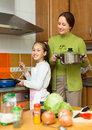 Mother with daughter cooking at kitchen