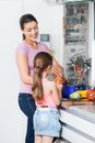 Mother and daughter cooking little girl preparing dinner at home in the kitchen Royalty Free Stock Photo