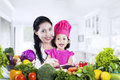 Mother and daughter cooking vegetable salad happy together Royalty Free Stock Image