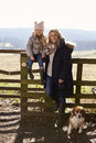 Mother and daughter by a country gate with pet dog, vertical Royalty Free Stock Photo