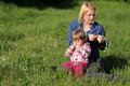 Mother and daughter creating flower wreaths in the park in spring Stock Photo