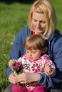 Mother and daughter creating flower wreaths in the park in spring Royalty Free Stock Image