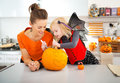 Mother with daughter creating jack o lantern on halloween young in bat costume big orange pumpkin party in decorated kitchen Stock Photo
