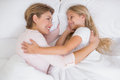 Mother and daughter cuddling in bed Royalty Free Stock Photo