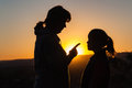 Mother daughter discipline silhouetted showing instruction finger to her sunset Stock Photos