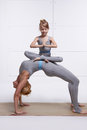 Mother and daughter doing yoga exercise, fitness gym wearing same woman standing in posture of bridge hands and feet resting on th
