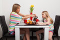 Mother and daughter drink tea have teatime at home red cups yellow tulips Stock Image