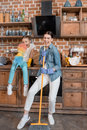 Mother and daughter with duster and broom having fun while cleaning home