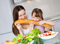 Mother and daughter eat bread Stock Images