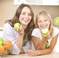 Mother with Daughter eating Apples Stock Photos