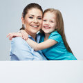Mother and daughter embrace business woman with kid girl iso studio portrait behind white board female model Stock Images