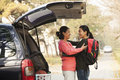 Mother and daughter embracing behind car on college campus Royalty Free Stock Images