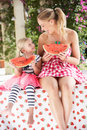 Mother And Daughter Enjoying Slices Of Water Melon Stock Photos