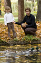 Mother and daughter feeds duck over pond Royalty Free Stock Image
