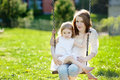 Mother and daughter on garden swing Stock Photo