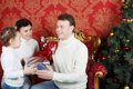 Mother and daughter give gifts to father near christmas tree in red room Stock Images