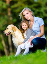 Mother and daughter with golden retriever are on the green grass sitting at summer park Royalty Free Stock Image