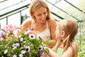 Mother and daughter growing plants in greenhouse looking at each other smiling Royalty Free Stock Photo
