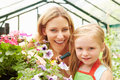 Mother and daughter growing plants in greenhouse looking to camera smiling Royalty Free Stock Photo
