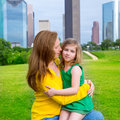 Mother and daughter happy hug in park at city skyline modern background Royalty Free Stock Image
