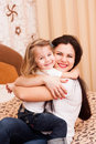 Mother and daughter have fun at home young hugs her cute little family portrait Royalty Free Stock Images