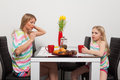 Mother and daughter have teatime at home drink tea red cups yellow tulips Stock Image