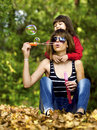 Mother and daughter having fun in the park with soap bubbles Royalty Free Stock Photography
