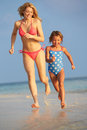 Mother and daughter having fun in sea on beach holiday playing Stock Photos