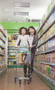 Mother and Daughter Having Fun in Supermarket, Pushing Cart Royalty Free Stock Photo