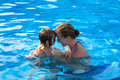 Mother and daughter having fun time in the pool doughter head to head passionate great swimming Royalty Free Stock Photography